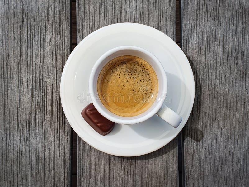 Tazza di caffè espresso con la piccola pralina del cioccolato sulla tavola grigia rustica Vista superiore fotografia stock