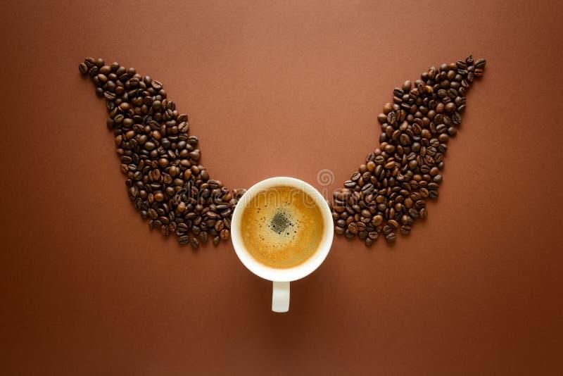 Tazza di caffè espresso con le ali dai chicchi di caffè su fondo marrone Concetto di buongiorno Vista superiore Disposizione pian fotografie stock libere da diritti