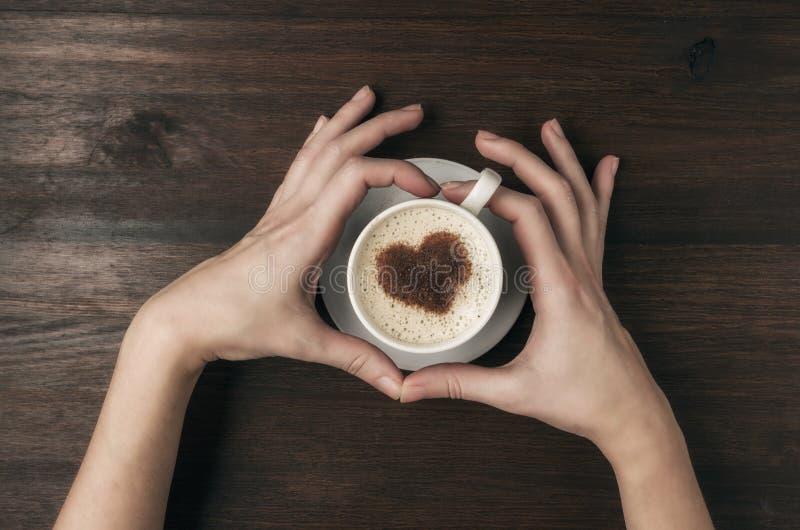 Tazza di caffè femminile della tenuta della mano con forma del cuore sulla tavola di legno immagine stock libera da diritti