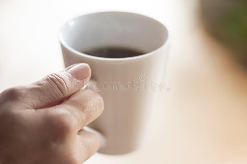 Tazza di caffè femminile della tenuta della mano immagini stock
