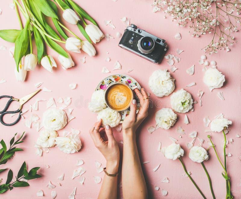 Tazza di caffè, fiori e macchina da presa femminili della tenuta delle mani fotografia stock