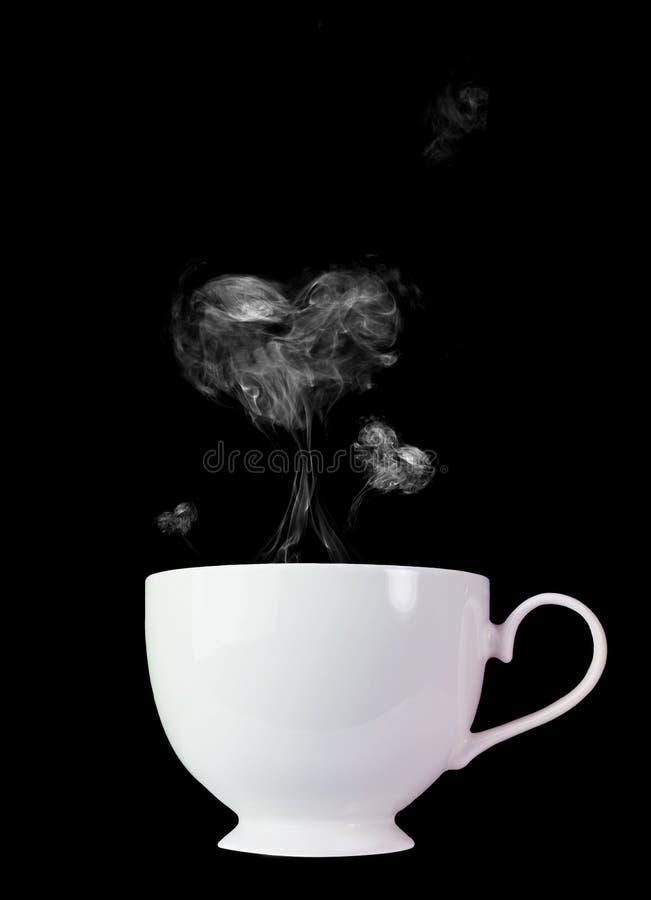 Tazza di caffè macchiato con fumo bianco, forma del cuore su un fondo nero fotografie stock libere da diritti