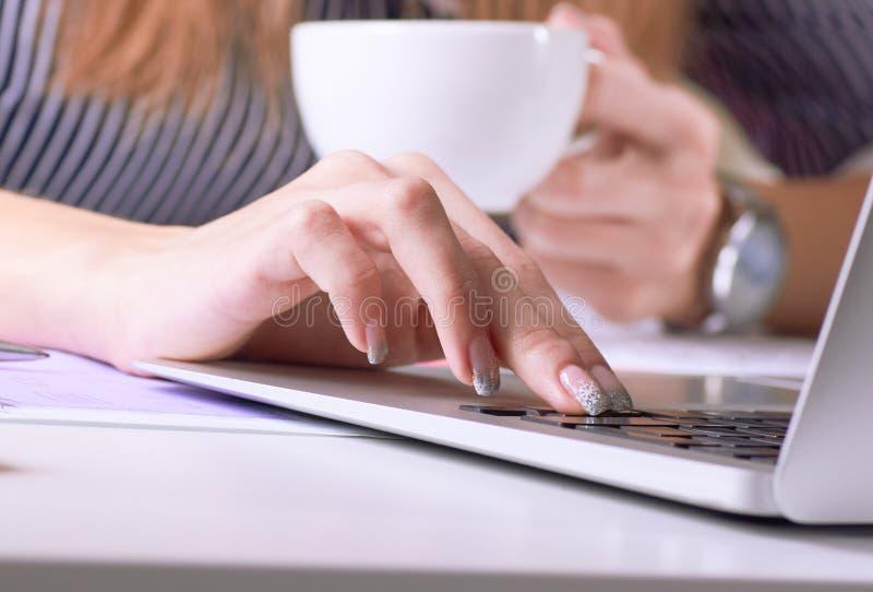 Tazza di caffè in mano della donna di affari Giovane donna che lavora con i documenti ed il primo piano del computer portatile fotografie stock