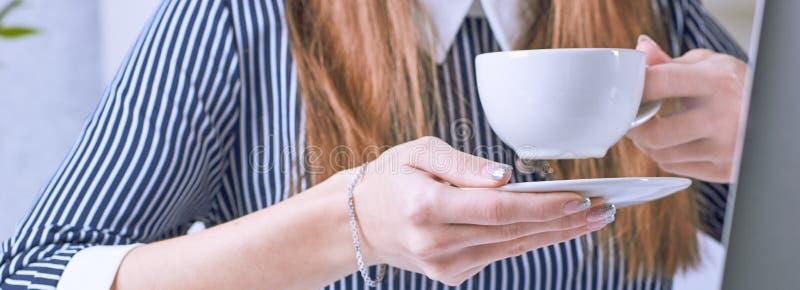 Tazza di caffè in mano della donna di affari Giovane donna che lavora con i documenti ed il primo piano del computer portatile immagine stock libera da diritti
