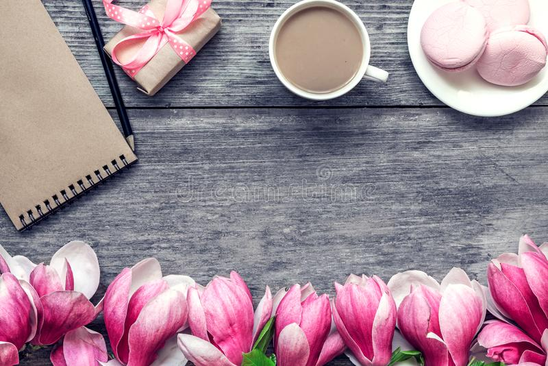 Tazza di caffè di mattina con latte, macaron del dolce, regalo o scatola e fiori attuali della magnolia sulla tavola di legno rus fotografie stock