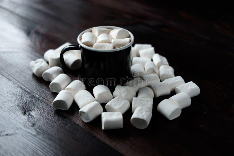 Tazza di caffè nera con le caramelle gommosa e molle fra le caramelle gommosa e molle su legno fotografie stock
