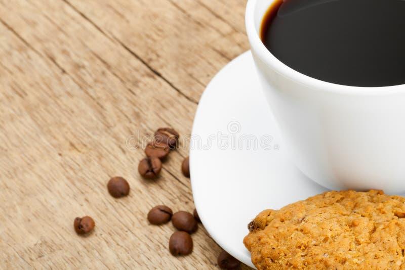 Tazza di caffè nero con i biscotti sulla vecchia tavola di legno immagini stock libere da diritti