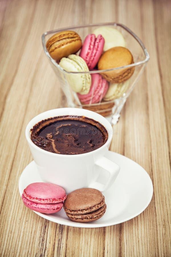 Tazza di caffè nero con i macarons variopinti francesi fotografia stock
