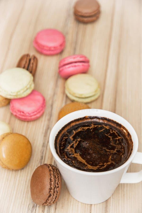 Tazza di caffè nero con i macarons variopinti francesi, delizia dolce immagini stock libere da diritti