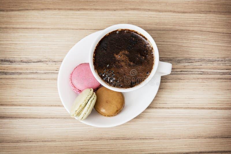 Tazza di caffè nero con i macarons variopinti francesi saporiti, d dolce fotografia stock