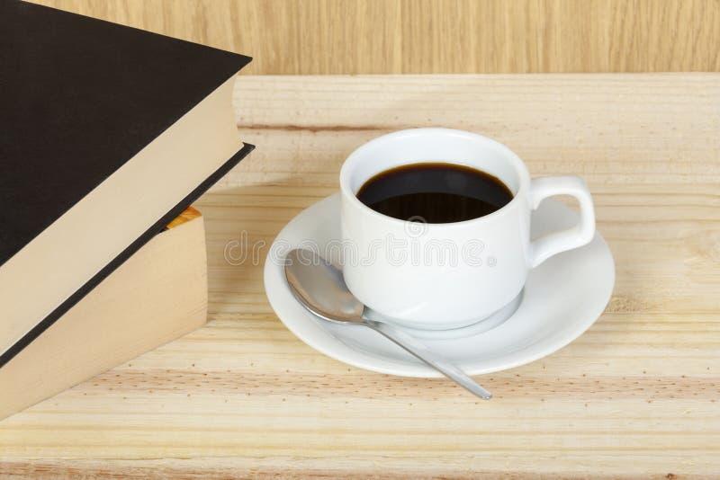 Tazza di caffè nero sulla tavola con i libri di lettura fotografie stock libere da diritti