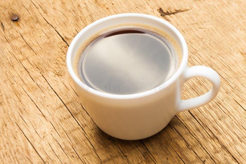 Tazza di caffè nero sulla vecchia tavola di legno - colpo dello studio fotografia stock libera da diritti