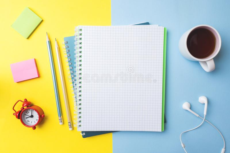 Tazza di caffè pulita della matita e del taccuino e un orologio con lo spazio della copia sul fondo blu giallo per la presentazio immagini stock libere da diritti