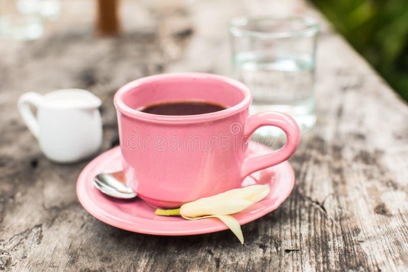 Tazza di caffè rosa sulla tavola di legno fotografie stock libere da diritti