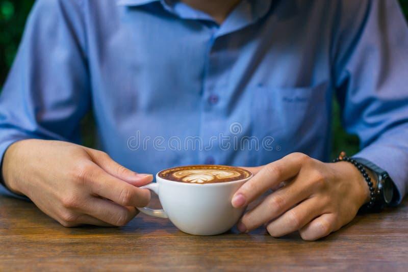 Tazza di caffè di seduta e della tenuta dell'uomo di affari immagine stock libera da diritti