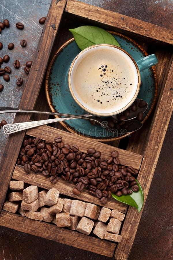 Tazza di caffè, semi di cacao torrefatti e zucchero bruno fotografie stock
