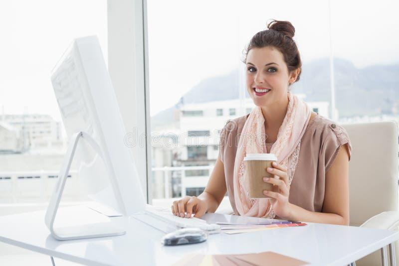 Tazza di caffè sorridente della carta della tenuta della donna di affari fotografia stock libera da diritti