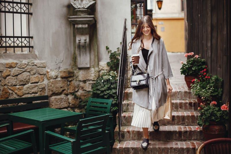 Tazza di caffè splendida e borsa della tenuta della giovane donna, sorridenti e immagini stock