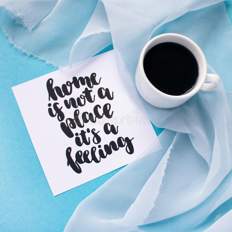 Tazza di caffè sul panno chiffon pastello blu-chiaro su un fondo blu La carta con la casa ispiratrice scritta a mano di citazione immagine stock libera da diritti