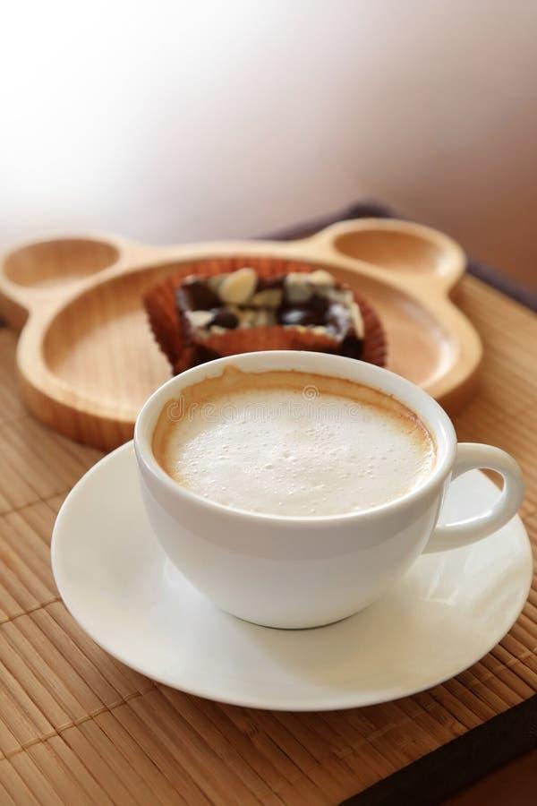 Tazza di caffè sulla tavola di legno con l'atmosfera dei confettieri fotografia stock