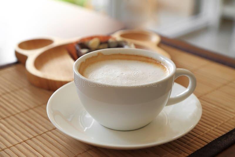 Tazza di caffè sulla tavola di legno con l'atmosfera dei confettieri immagine stock