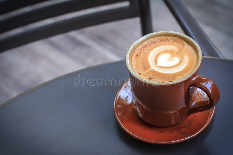 Tazza di caffè sulla tavola nera del metallo in caffetteria con il fondo di legno del pavimento immagine stock libera da diritti