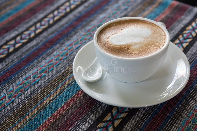 Tazza di caffè sulla tovaglia fotografia stock