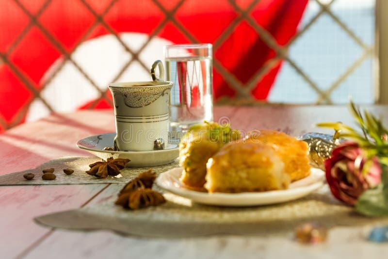 Tazza di caffè turco e di un piatto con baklava e la bandiera del turco fotografia stock libera da diritti