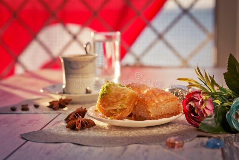 Tazza di caffè turco e di un piatto con baklava e la bandiera del turco fotografie stock libere da diritti