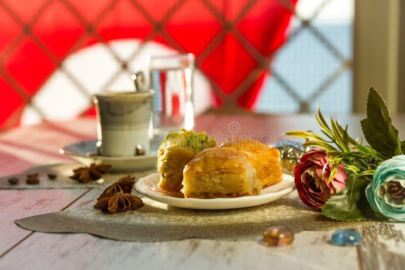 Tazza di caffè turco e di un piatto con baklava e la bandiera del turco immagini stock