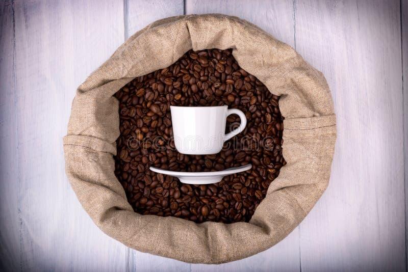 Tazza di caffè in una borsa in pieno dei chicchi di caffè immagine stock libera da diritti
