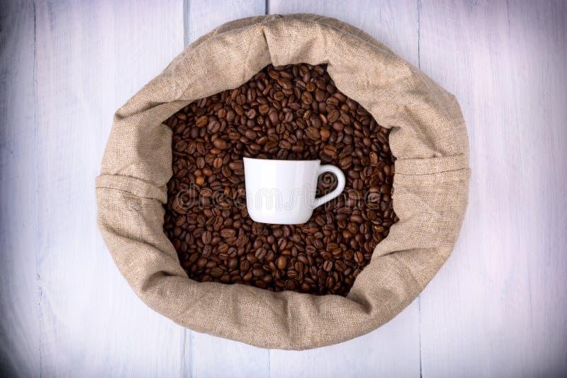 Tazza di caffè in una borsa in pieno dei chicchi di caffè fotografie stock libere da diritti