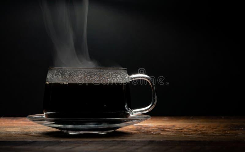 Tazza di caffè di vetro di Lit superiore su fondo nero fotografia stock