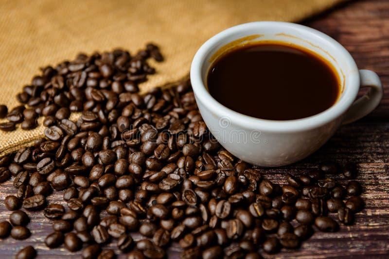 tazza di caff? con i fagioli su fondo di legno fotografia stock