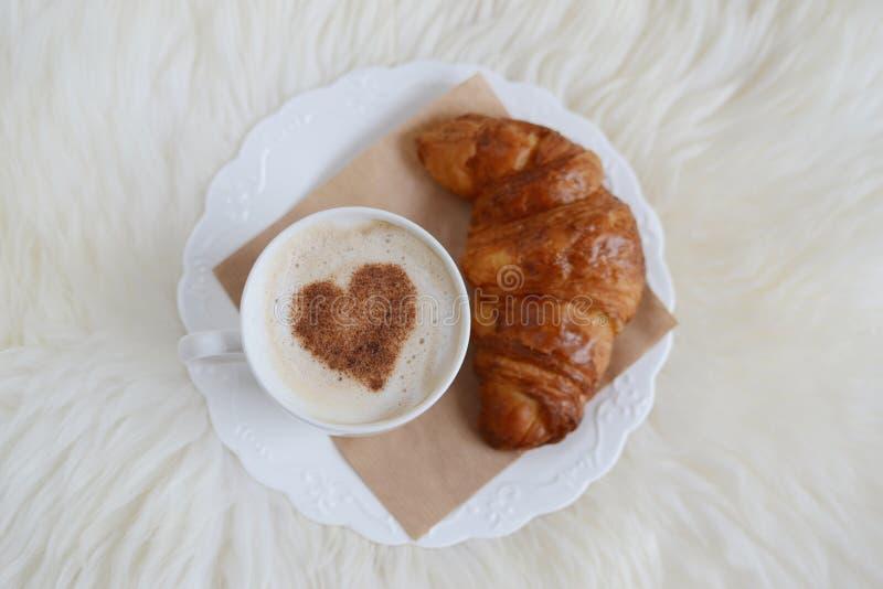 Tazza di cappuccino con il modello del cuore di cannella e del croissant fotografia stock