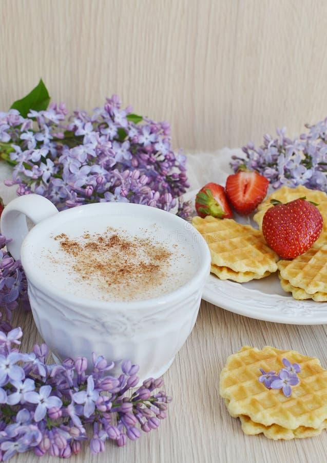 Tazza di cappuccino con le cialde, le fragole ed i fiori fotografie stock