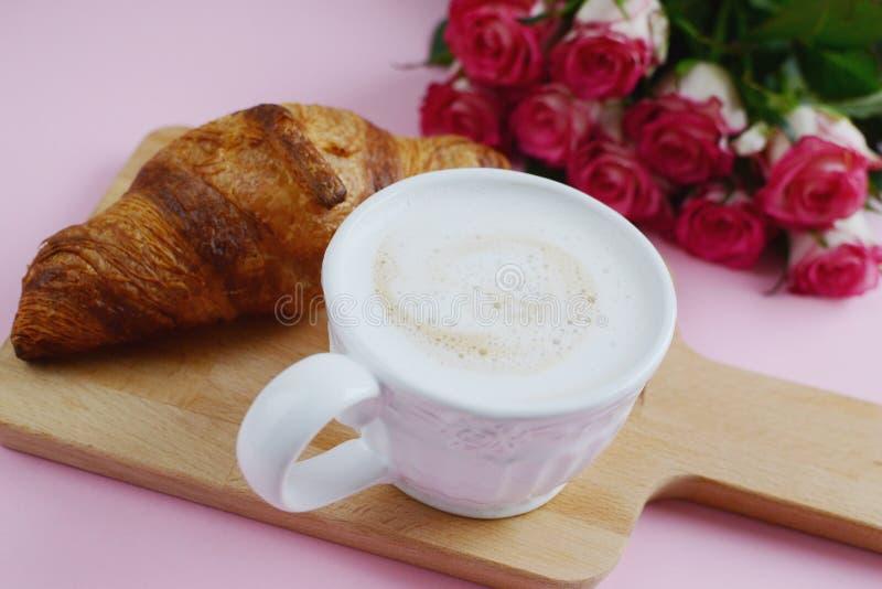 Tazza di cappuccino e del croissant squisito con le rose rosa immagine stock libera da diritti