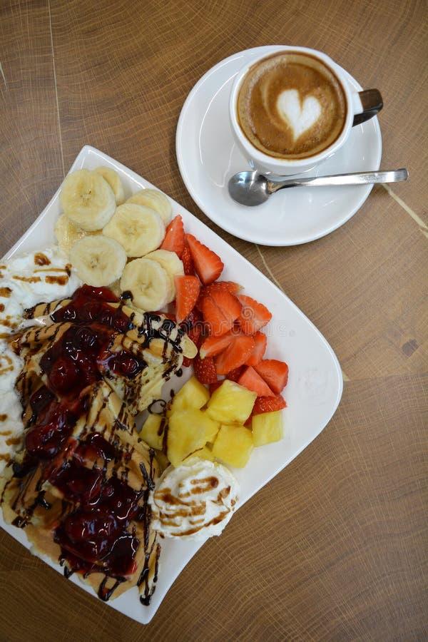 Tazza di cappuccino e delle cialde spumosi con frutta e crema fotografie stock libere da diritti