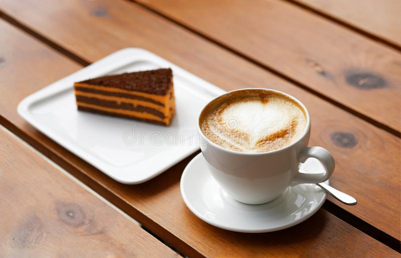 Tazza di cappuccino e pezzo di dolce a strisce su una tavola di legno fotografia stock libera da diritti