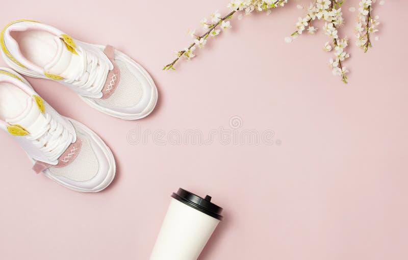 Tazza di carta alla moda femminile delle scarpe da tennis, del caffè o del tè e rami della molla dei fiori bianchi sulla disposiz fotografia stock