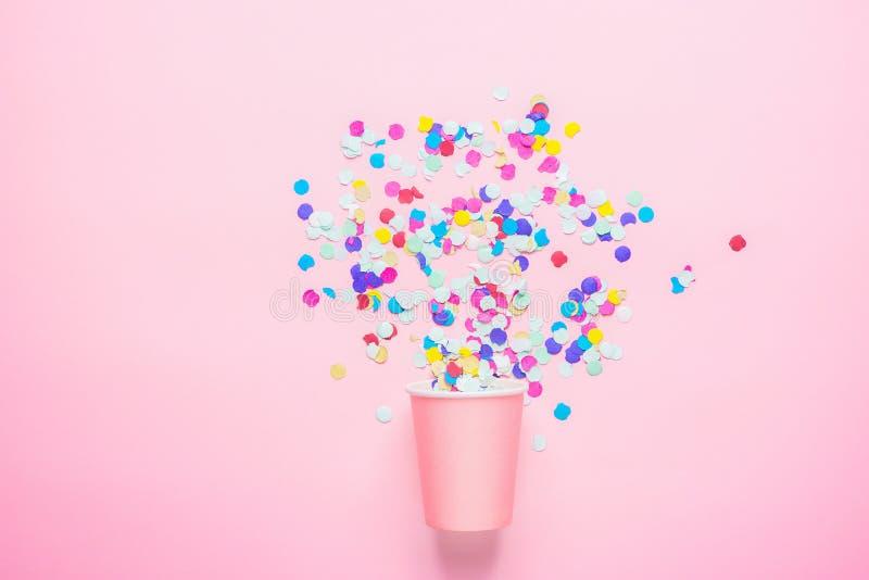 Tazza di carta bevente con i coriandoli multicolori sparsi su fondo fucsia Composizione piana in disposizione Celebrazione della  immagine stock