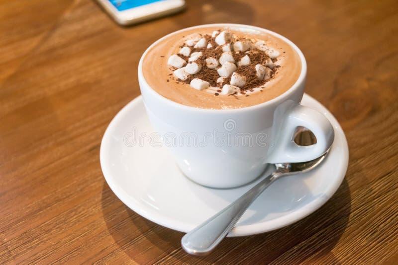 Tazza di cioccolata calda con le caramelle gommosa e molle e lo smartphone sulla tavola di legno fotografia stock