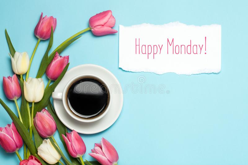Tazza di coffe e tulipani rosa su fondo blu Parole lunedì felice Concetto del caffè della primavera Vista superiore, disposizione immagini stock