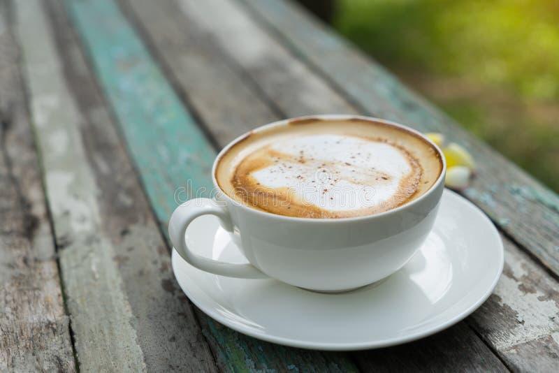 Tazza di Coffe sulla vecchia tavola di legno in parco immagini stock libere da diritti