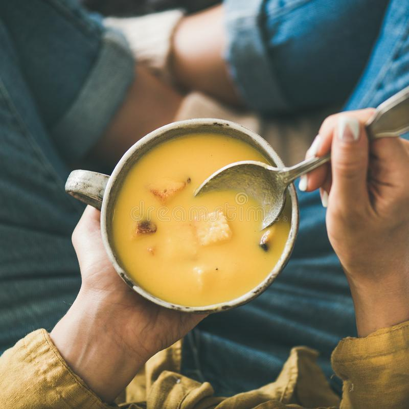 Tazza di conservazione femminile della minestra di riscaldamento della crema della zucca, il raccolto quadrato immagine stock libera da diritti