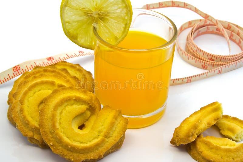 Tazza di Juice With Cookies arancio e del nastro di misurazione isolati sopra immagini stock libere da diritti