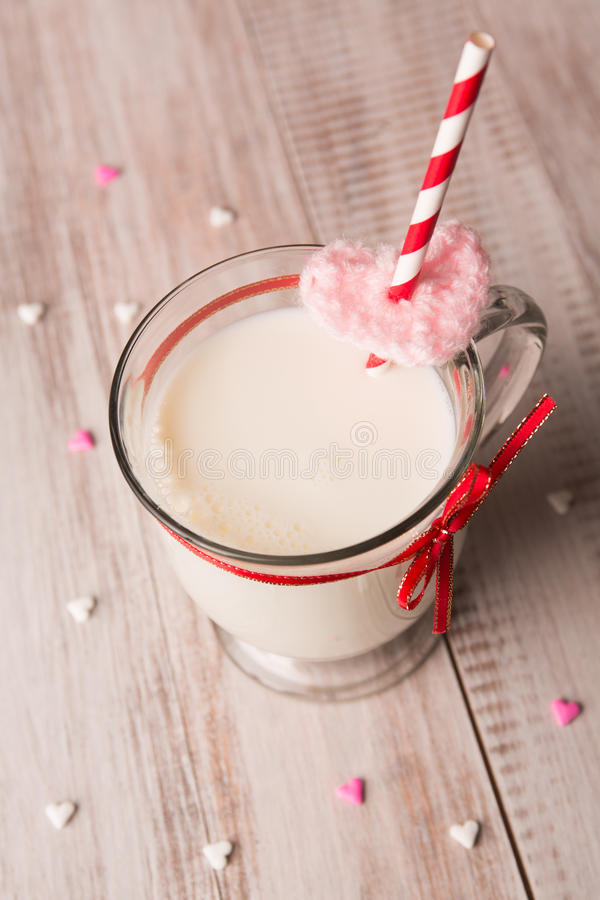 Tazza di latte e di cuori per il giorno di biglietti di S. Valentino immagine stock