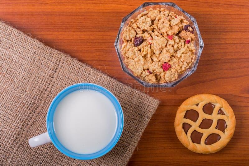 Tazza di latte su una tavola di legno con i cereali e la crostata del cioccolato fotografia stock libera da diritti