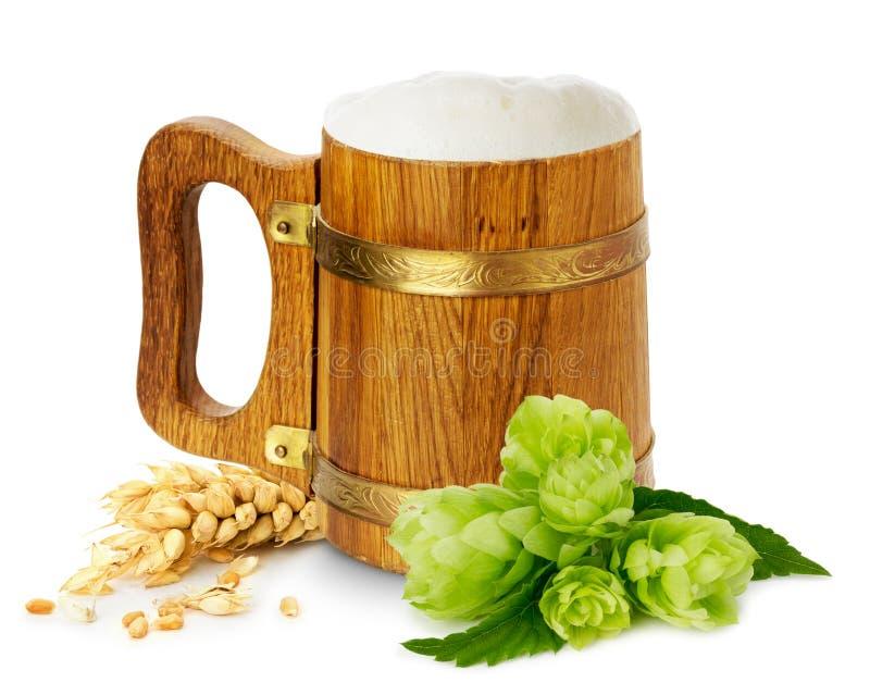 Tazza di legno con birra, il luppolo di verde ed il grano fotografie stock