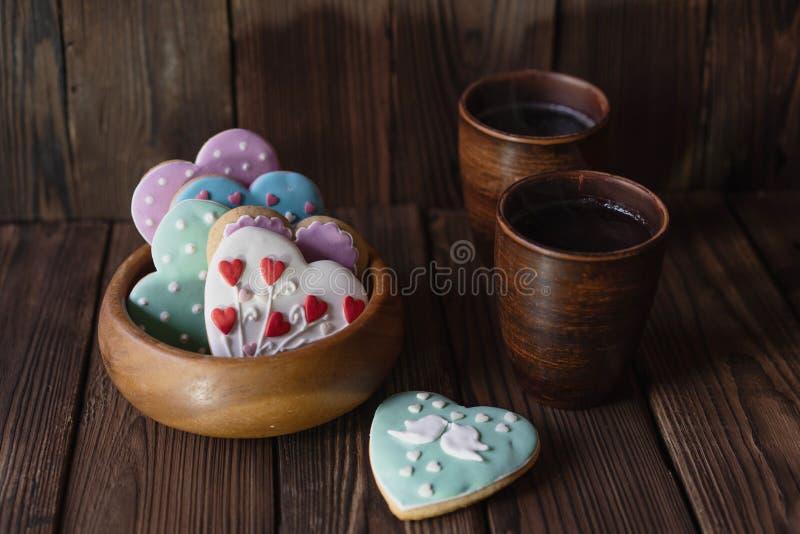 Tazza di legno con i cuori del pan di zenzero e le tazze lustrati di tè fotografia stock
